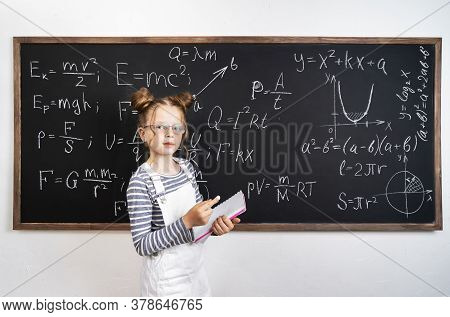 Back To School: A Schoolgirl Stands At The Blackboard And Holds Notebooks And Textbooks In Her Hands