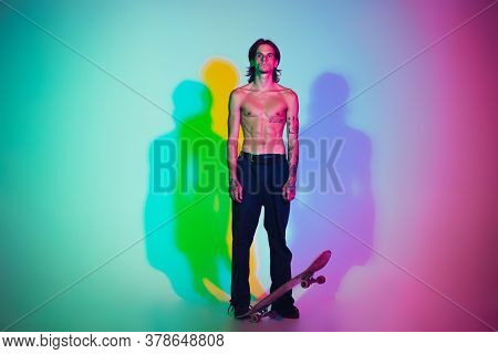 Skateboarder With Board Isolated On Studio Background In Colorful Neon Light. Young Man Shirtless Ri