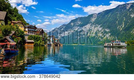 Hallstatt, Austria. Lakeside town in the Austrian Alps. Classic postcard view of famous landscape with passenger ship on a water. Beautiful sunny day with blue sky and clouds. Salzkammergut region.