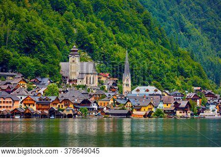 Hallstatt village on Hallstatter lake in Austria. High Alpine mountains. Picturesque Austrian Alps panorama scenery with green forest trees on hills. Summer view. UNESCO world heritage site.