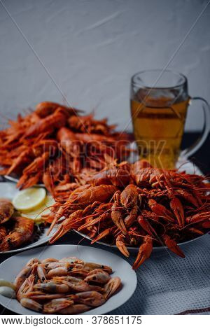 Two Large White Plates With Boiled Crawfish, Boiled Shrimps, Grilled Lobster And Glass Of Beer On A