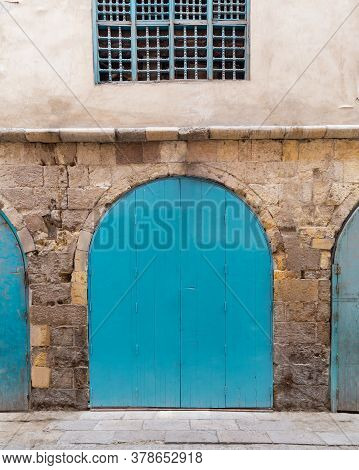 Closed Turquoise Weathered Wooden Arched Door And Wood Window Grill In Stone Bricks Wall, Located In