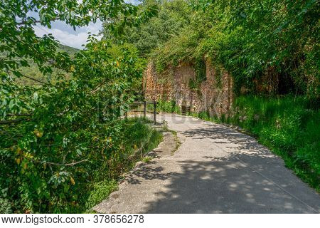 View Of A Nice Country Road With A Stone Wall, A Wooden Railing And Lots Of Greenery. Tranquility Co