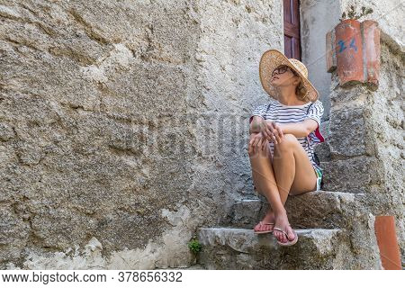 Beautiful Female Tourist Wearing Big Straw Sun Hat And Shorts Sitting And Relaxing On Old Stone Hous