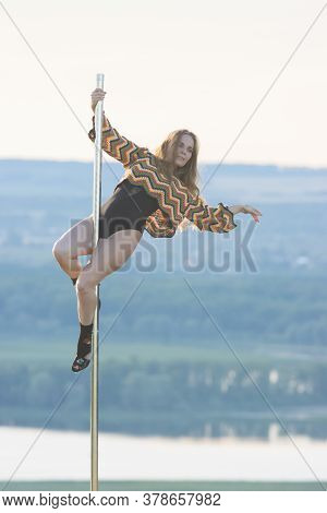 Young Woman Dancer On High Heels Holding By The Pole And Posing On The Pole