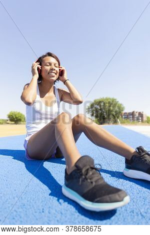 Woman In A Tank Top And Shorts Smiling As She Listens To Music Through Her Headphones. Space For Tex