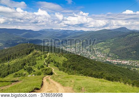 Mountain Summer Landscape. Trail Among The Forest Against The Background Of Mountain Peaks And  Sky.