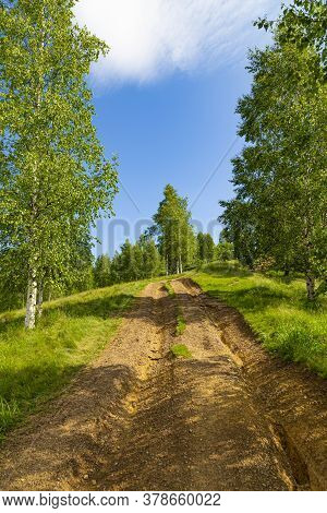 Mountain Summer Landscape. Road Uphill. Trail Among The Trees Against The Background Of   Sky. View