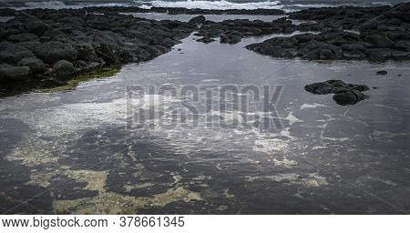 Waterway From The Beach Towards The Sea Between Rock Formations