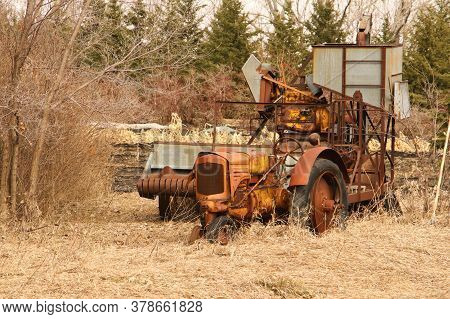 An Old Abandoned Tractor And Pull Behind Combine.