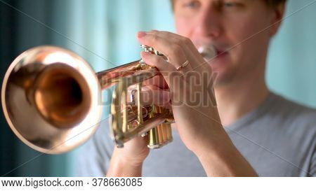 A Young Man Plays The Trumpet. Hands Of Musician. Close Up View.