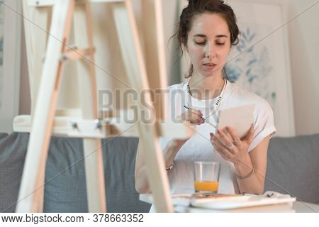 Beautiful Woman Is Sitting On Sofa, Holding Paintbrush, Colored Polish, Artist In White T-shirt. Eas
