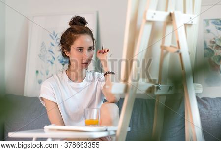 Beautiful Woman Sitting Sofa, Holding Paintbrush, Serious Look Evaluating Picture, Artist White T-sh