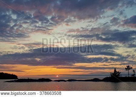 The Sun Goes Over Horizon, A Beautiful Sunset Over The Lake, Clouds In The Blue Sky. Horizontal Phot
