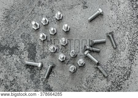 Several Bolts Lie And Stand (with Their Caps Down) On A Light Concrete Surface, Top View.