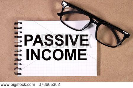 Inscription On White Belt Passive Income. Glasses Are On The Paper