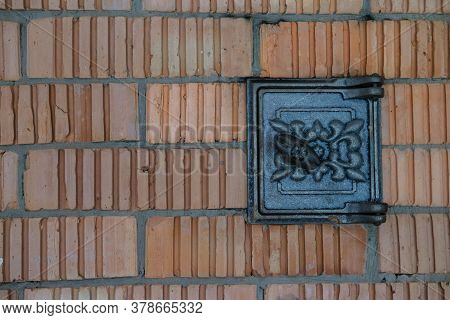 Black Metal Door For Cleaning A Wood Stove Or Fireplace From Soot And Dirt, On A Background Of Red B