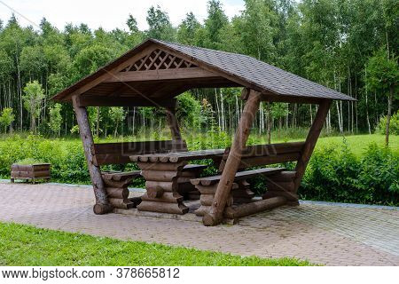 A Roadside Gazebo For Tourists, Made Of Logs, Stands On A Wide Cobblestone Path Against The Backdrop