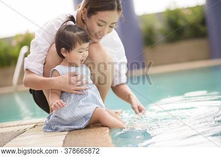 A Happy Asian Mother And Daughter Are Enjoy Swimming In Pool , Lifestyle, Parenthood, Family Concept