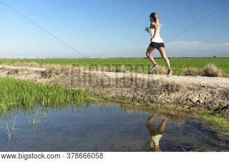 A Young Athlete Girl In A Yellow Shirt Running Down A Path Between Rice Fields, With Her Reflection