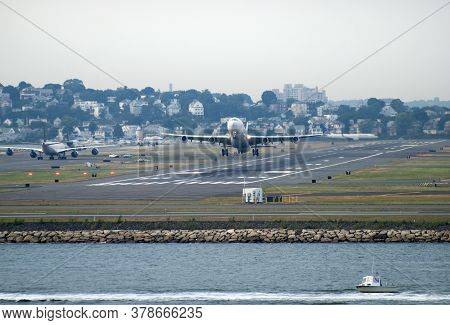 The Motorboat Passing By Boston Airport While The Airplane Is Taking Off (massachusetts).