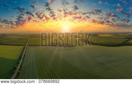 Aerial View Of The Sunset Over The Green Fields.