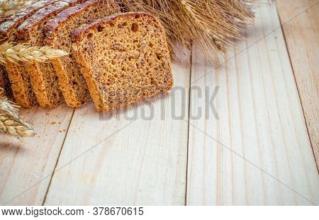 Rustic Rye. Fresh Loaf Of Rustic Traditional Bread With Wheat Grain Ear Or Spike Plant On Wooden Tex