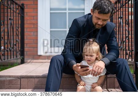 Caucasian Man In A Business Suit Looks At The Mobile Screen With Daughter On The Stairs. A Little Gi