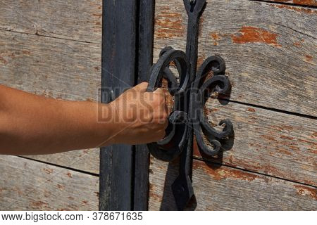 Women Opens An Ancient Wooden Door Decorated With Wrought Iron Elements. Old Lock With An Iron Handl