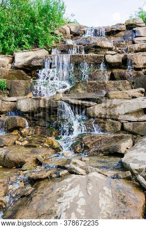 River Waterfall. Small Jets Of Water Flow Down The Stones On A Sunny Day