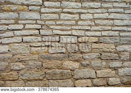 Texture Of Old Masonry Made Of Natural Raw Stone. The Wall Is Built Of Brown Stone,