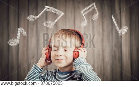 Little Boy On Wooden Background With Red Headphones