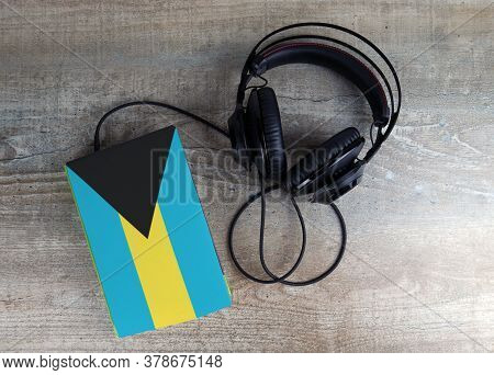 Headphones And Book. The Book Has A Cover In The Form Of Bahamas Flag. Concept Audiobooks. Learning
