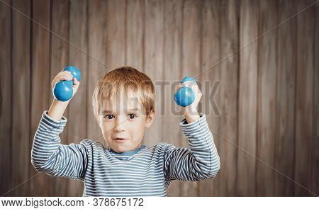 Child Holding Dumbbells Indoors On Wooden Background.