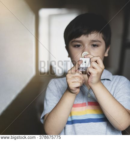 Blurry Face Of Kid Holding One Pound Coin And White Paper Dice Showing Number One With Copy Space Fo