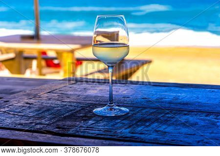 A Glass Of White Wine On Wooden Table Of Outdoor Restaurant On The Beach. Sea View. Summer Beach Vac