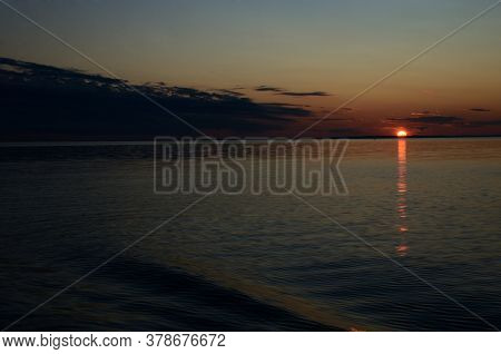 Beautiful Sunset In The Twilight Sky Over The Lake, The Sun Sets Over The Horizon, The Sun Path Is R