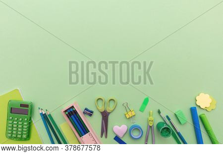 School Supplies On Green Color Background, Top View, Copy Space