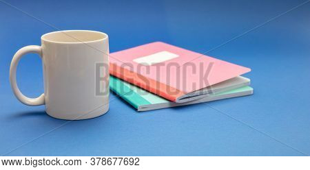 Mug White Color And School Notebooks On Blue Background. Kids Homework Soft Drink