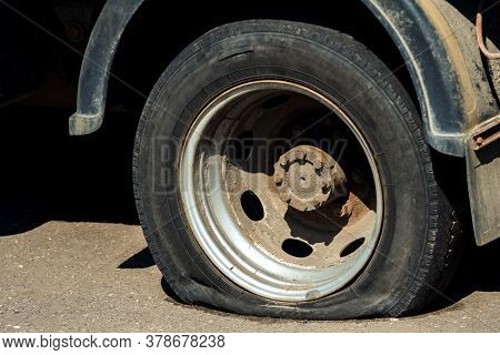 Blown Away A Dirty Rusty Car Wheel Truck. There Are Signs Of Deliberate Damage To The Wheel.