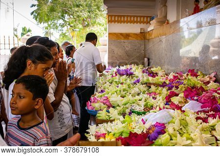 Pilgrims Lay Flowers In A Buddhist Temple. Flower Offerings To Buddha Inside The Temple Of The Sacre