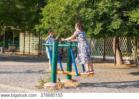 Anapa, Russia-05.07.2020: Mom And Child Swing On A Swing In The Park. Sports Equipment For Two Peopl