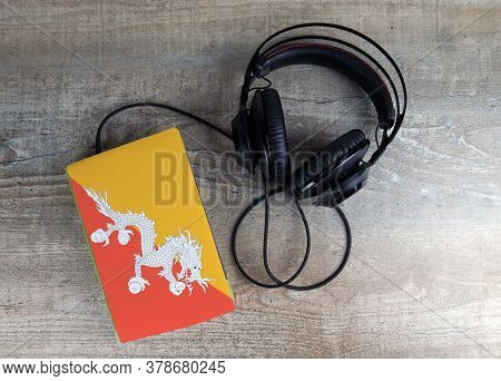 Headphones And Book. The Book Has A Cover In The Form Of Bhutan Flag. Concept Audiobooks. Learning L