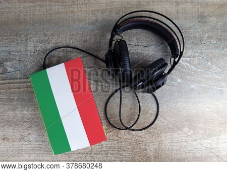 Headphones And Book. The Book Has A Cover In The Form Of Hungary Flag. Concept Audiobooks. Learning