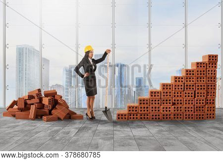 Businesswoman With Helmet Builds A Growing Stats Bar With Bricks
