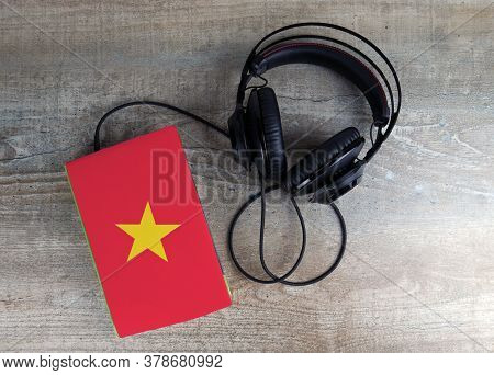 Headphones And Book. The Book Has A Cover In The Form Of Vietnam Flag. Concept Audiobooks. Learning
