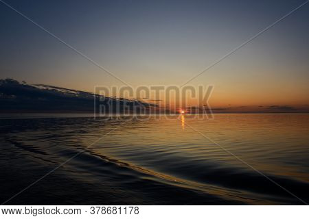 Beautiful Sunset In Twilight Sky Over The Lake, The Sun Sets Over The Horizon