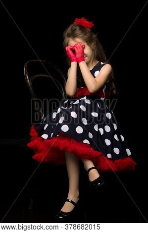 Beautiful Girl In Retro Style With Polka Dots, Red Gloves And A Bow Posing On Camera. She Folded Her