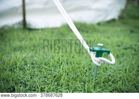 Close Up Of Tent Peg Anchor On The Ground Tent, Hook Of Tent, Camping,nature Tourism Concept