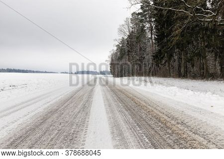 Narrow Unpaved Snow-covered Winter Road For Car Traffic, Overcast Sky On The Road, Snow On The Road